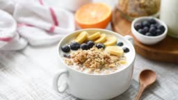 Granola with milk and fresh fruits in bowl