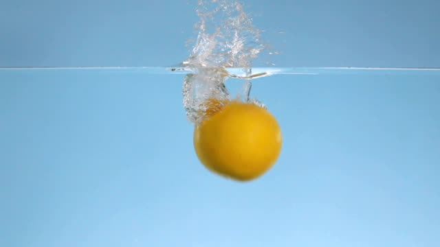 grapefruits dropped into water in slow motion - small group of objects stock videos & royalty-free footage