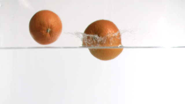 Grapefruits falling into water in super slow motion