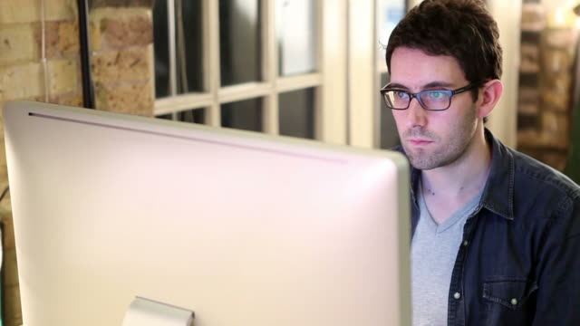 graphic designer gazes at computer screen - one mid adult man only stock videos & royalty-free footage