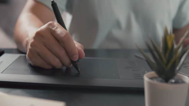 vidéos et rushes de illustrateur de concepteur graphique travaillant sur l'ordinateur portatif avec la tablette graphique. - stylo
