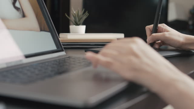 graphic designer working on laptop with graphics tablet.photographer, compositing - pen stock videos & royalty-free footage