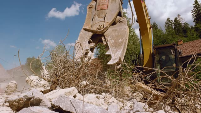 SLO MO Grapple on the excavator picking up wire from the pile of debris in sunshine