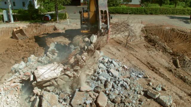 vídeos y material grabado en eventos de stock de antena cuchara de la excavadora clasificación de desechos de construcción - un solo hombre maduro