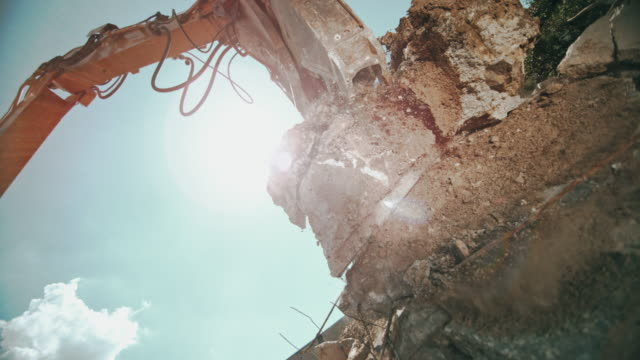 slo mo grapples placing concrete debris onto a pile at the sunny construction site - earth mover stock videos & royalty-free footage