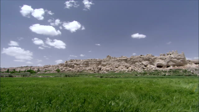 ws pan grass blowing in wind with abandoned village in distance, iran - cliff dwelling stock videos & royalty-free footage