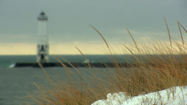 ws r/f grass growing on lakeshore, pier and lighthouse in background / michigan, usa - lakeshore stock videos & royalty-free footage