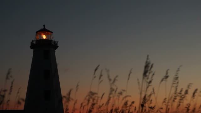 grass in forefront lighthouse under sunset in background - lighthouse stock videos & royalty-free footage