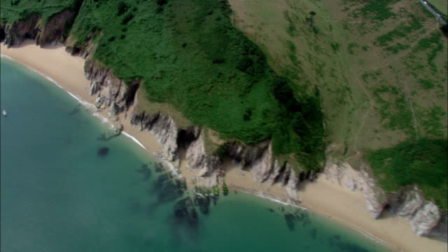 vídeos de stock, filmes e b-roll de grassy cliffs border a section of the southwest coast of england. available in hd. - erodido