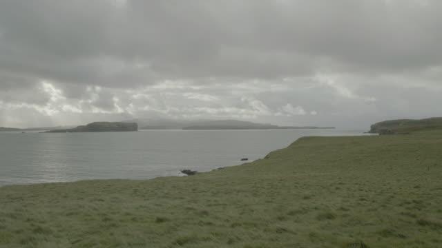 vidéos et rushes de grassy coastline looking out to ocean; isle of skye, scotland, uk - îles hébrides