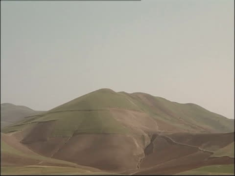 grassy desert hills rise above the afghanistan desert. - afghanistan stock videos and b-roll footage