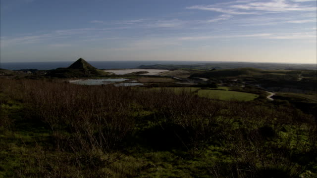 vídeos de stock e filmes b-roll de grassy land leading towards a pyramid of earth created by china clay pit works, cornwall. available in hd. - pyramid