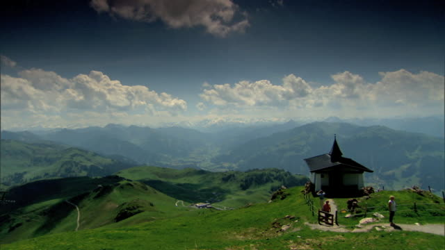 ws grassy mountain plateau w/ quaint small church people standing on dirt pathway in front of building overlooking valley wide expanse of mountains... - tyrol state austria stock videos and b-roll footage