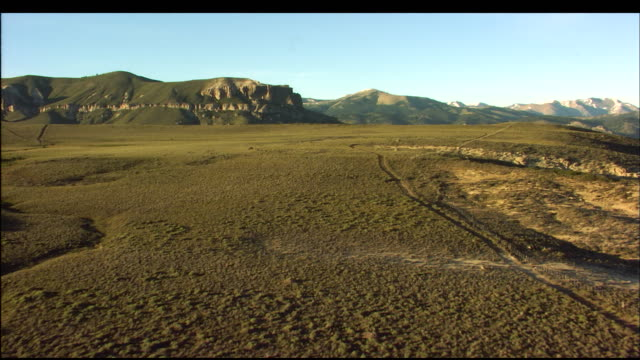 a grassy plateau gives way to a deep mountain valley. - altopiano video stock e b–roll