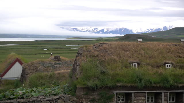 grassy rooftops in front of cloudy mountainscape - iceland stock videos & royalty-free footage