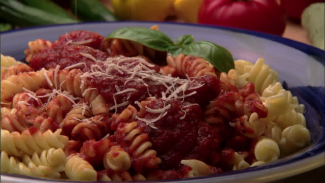 ecu, zo, grated cheese being sprinkled into pasta with tomato sauce, fresh vegetables in background  - grated stock videos & royalty-free footage