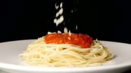 SLOW MOTION: Grated parmesan falls on a hot spaghetti with sauce