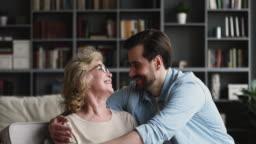 Grateful loving adult son embracing mature mum at home