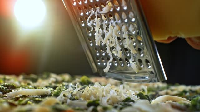 vidéos et rushes de slo mo fromage râpant sur une pizza aux légumes - cheese