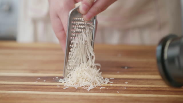 grating parmesan cheese on wooden chopping board - parmesan stock videos & royalty-free footage