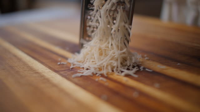 grating parmesan cheese on wooden chopping board - italian culture stock videos & royalty-free footage