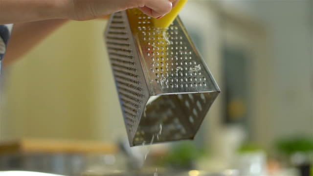 Grating yellow cheese with a metal grater, slo mo