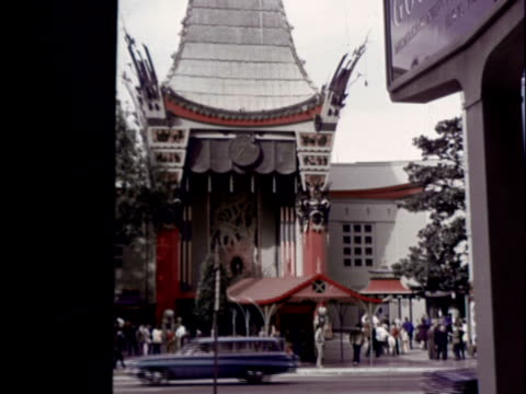 vidéos et rushes de grauman's chinese theater aka mann's chinese theater cars passing along hollywood boulevard in front / celebrity autographs handprints and footprints... - 1970