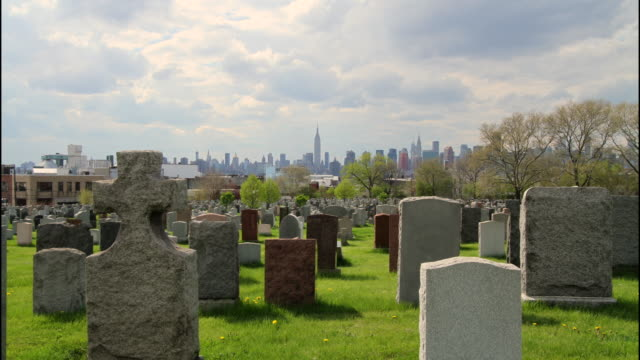 vídeos de stock e filmes b-roll de grave stones in queens with skyline - cemitério