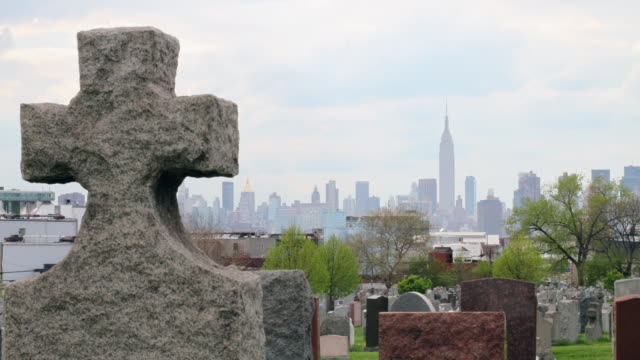 grave stones in queens with skyline - tomba luogo di sepoltura video stock e b–roll