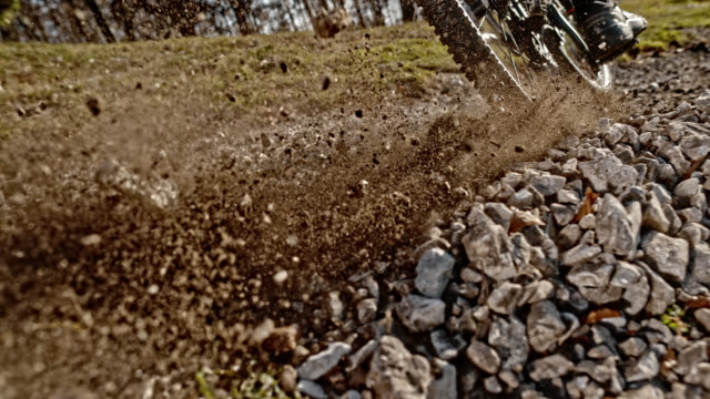 speed ramp gravel being pushed into the air in sunshine by the back wheel of the mountain bike - mountain bike video stock e b–roll