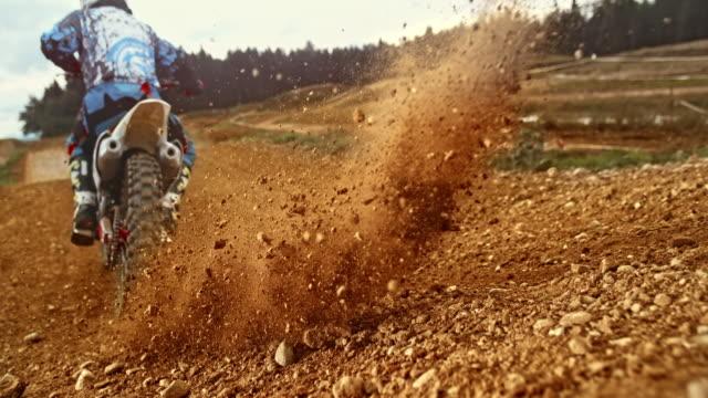 vídeos de stock, filmes e b-roll de rampa de velocidade cascalho estourando como moto de motocross drives por - esportes extremos