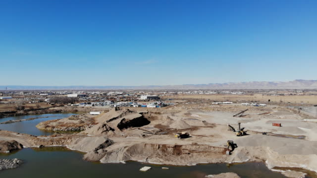 gravel pit heavy equipment and construction site industrial 4k drone areal video - pond stock videos & royalty-free footage