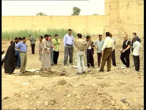 graves found in grounds of jail itn baghdad abu ghraib prison men digging in grounds of prison to reveal remains of executed prisoners in shallow... - execution bildbanksvideor och videomaterial från bakom kulisserna