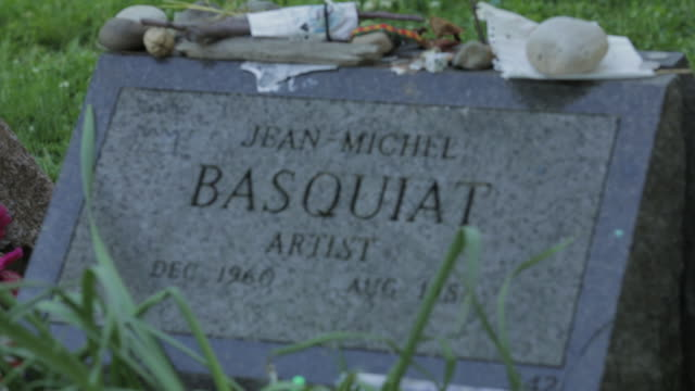 gravestone of artist jean-michel basquiat with rocks, sticks, dice & letters atop stone and tall grass blades in fg - モントリオール旧市街点の映像素材/bロール