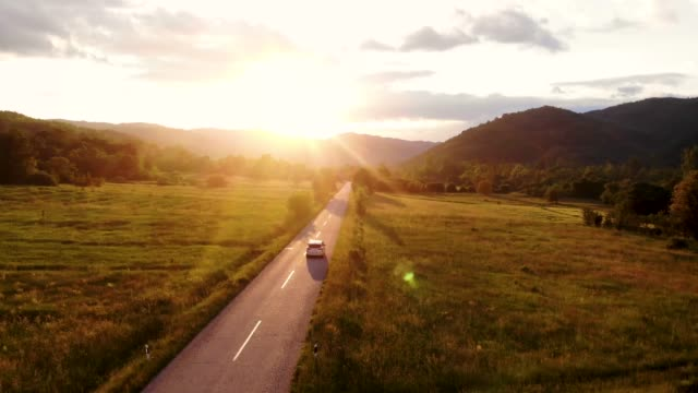 a gray car drives down an empty country road at a golden summer sunset - horizon over land stock videos & royalty-free footage