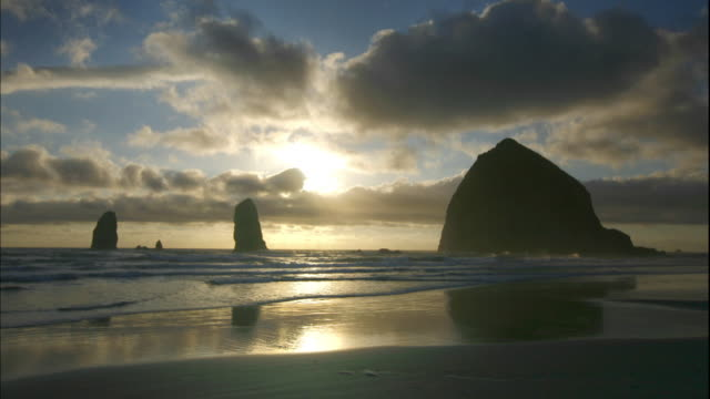 Gray clouds pass over Haystack Rock on Cannon Beach in Oregon.
