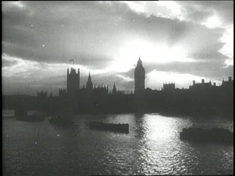 gray clouds settle over the silhouetted houses of parliament along the thames river in london - 1940 stock-videos und b-roll-filmmaterial