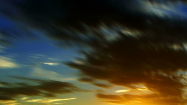 gray clouds streak and ripple across a sunset sky. - miglioramento digitale video stock e b–roll