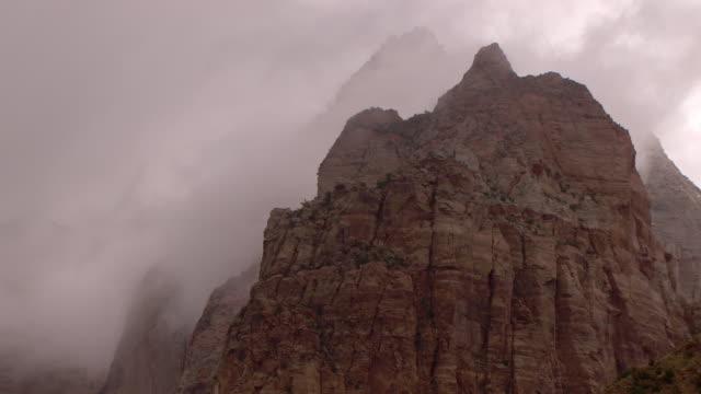 gray, misty clouds passing behind rugged mountain peak - ザイオン国立公園点の映像素材/bロール