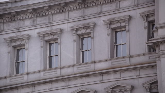 la a gray office building with a line of windows surrounded by ornate pediments / washington, district of columbia, united states - ペディメント点の映像素材/bロール