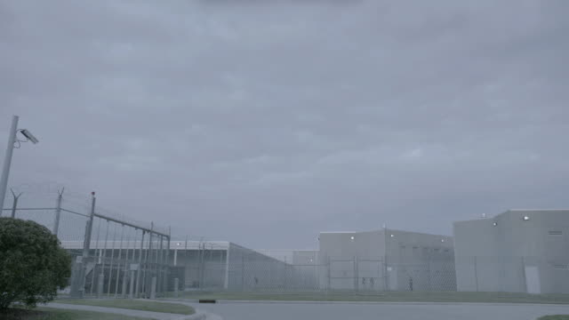 la gray prison buildings surrounded by chain link fencing / california, united states - prison fence stock videos & royalty-free footage
