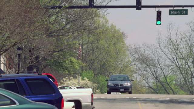 ms gray sedan driving in a small town street downhill, through green traffic light, and past parked cars / madison, georgia, united states - segnale per macchine e pedoni video stock e b–roll