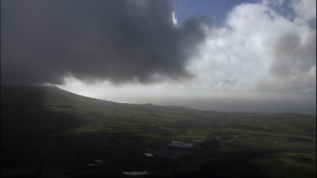 a gray storm cloud casts a shadow over the green farmlands of wales. - galles video stock e b–roll