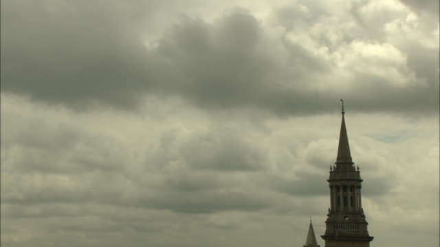 gray storm clouds gather over a church steeple in oxford, england. - steeple stock videos & royalty-free footage