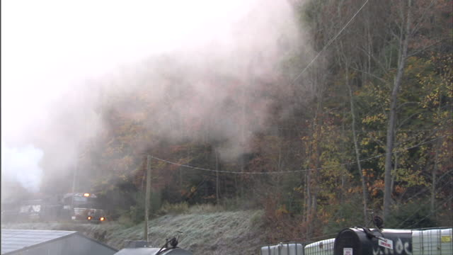Gray/white smoke moving from left across coal mine yard freight/coal train moving on Appalachian Mountains hillside BG white smoke out of stack...