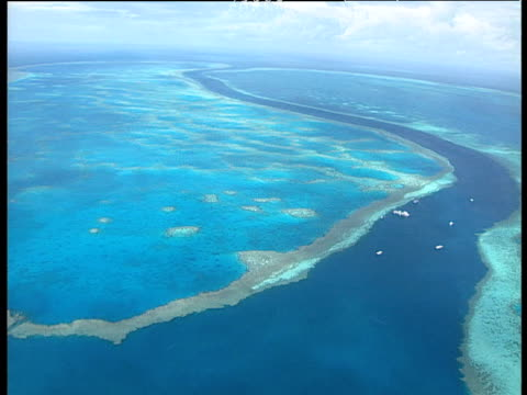 great barrier reef stretching out along surface of blue ocean tourist boats anchored just off the reef australia - anchored stock videos & royalty-free footage