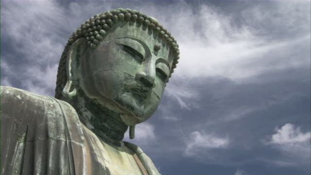 cu la great buddha at kotoku-in temple against sky with white wispy clouds / kamakura, kanagawa prefecture, japan - figura maschile video stock e b–roll