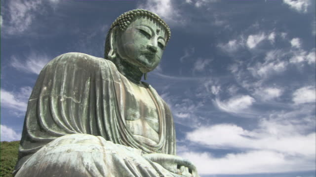 T/L MS LA Great Buddha at Kotoku-in temple against sky with white wispy clouds / Kamakura, Kanagawa Prefecture, Japan