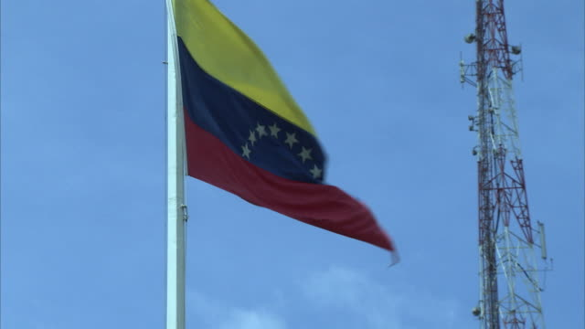 ms zo ws great colombian flag blowing in wind, telecommunication tower in background / cabimas, zulia, venezuela - colombian flag stock videos and b-roll footage