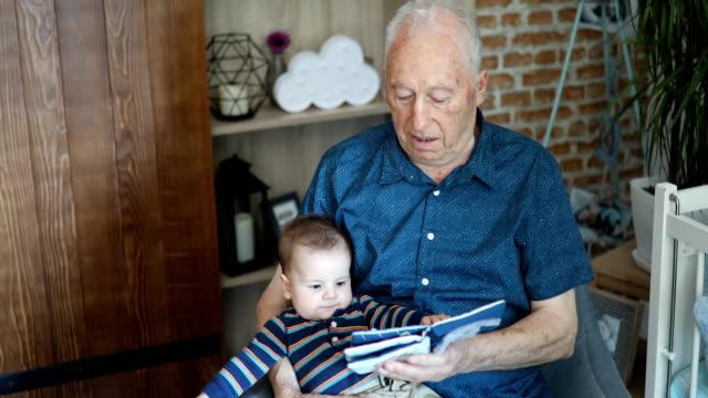 vídeos y material grabado en eventos de stock de gran abuelo mirando el librito de bebé con su bisnieto - abuelo